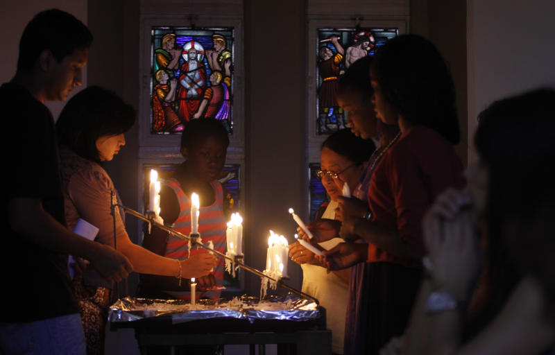 Worshippers light candles and dedicate prayers at the Rosebank Catholic Church in Johannesburg, Sunday, Dec. 16, 2012.  South Africa's former President Nelson Mandela underwent a successful surgery to remove gallstones Saturday, the nation's presidency said, as the 94-year-old anti-apartheid icon is still recovering from a lung infection. Doctors treating Mandela waited to perform the endoscopic surgery as they wanted to first attend to his lung ailment, presidential spokesman Mac Maharaj said in a statement. Mandela has been hospitalized since Dec. 8. (AP Photo/Denios Farrell)