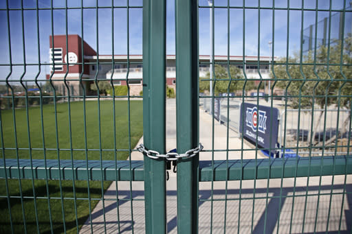 FILE - A gate at the Chicago Cubs practice facility at Sloan Park in Mesa, Ariz., is closed and locked due to the coronavirus, in this Monday, March 16, 2020, file photo. Big league managers say that Major League Baseball has instructed them to prepare for spring training to start on time in mid-February despite uncertainty around the coronavirus. Tampa Bay Rays manager Kevin Cash said Wednesday, Dec. 16, 2020, that officials from the commissioner's office had a meeting with managers Tuesday an expressed optimism about opening spring camps as scheduled. (AP Photo/Sue Ogrocki, File)