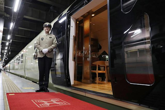<p>A crew member stands next to one of the entrances to the Train Suite Shiki-shima at Ueno Station in Tokyo. (Photo: STR/AFP/Getty Images) </p>
