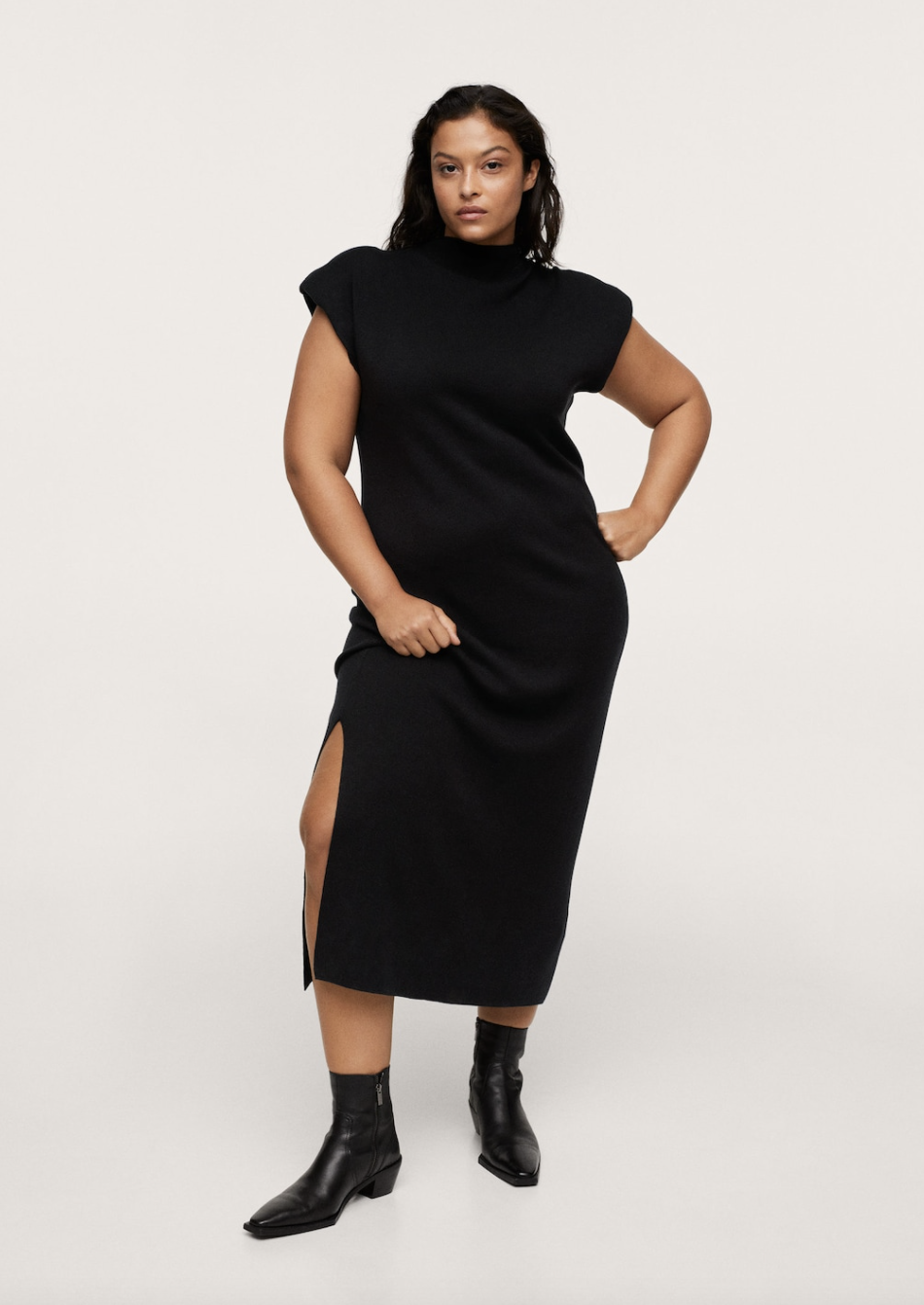 plus size model with black hair posing in black midi dress and black booties