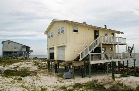 An abandoned beach home (R) sits on the Gulf Coast in Alligator Point, Florida, July 9, 2014. REUTERS/Phil Sears
