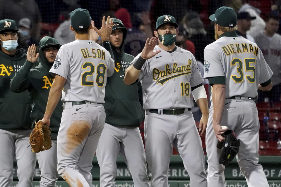 Oakland Athletics, including Mitch Moreland (18), congratulate each other after a 3-2 win over the Boston Red Sox in a baseball game Tuesday, May 11, 2021, in Boston. (AP Photo/Mary Schwalm)