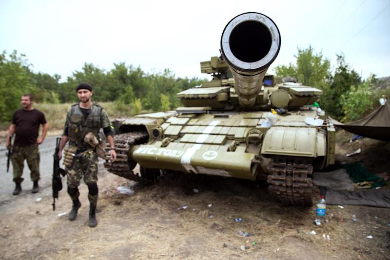 Ukrainian troops stand beside a tank as they guard a checkpoint near the Ukrainian city of Avdiyvka, north of Donetsk, on August 22, 2014