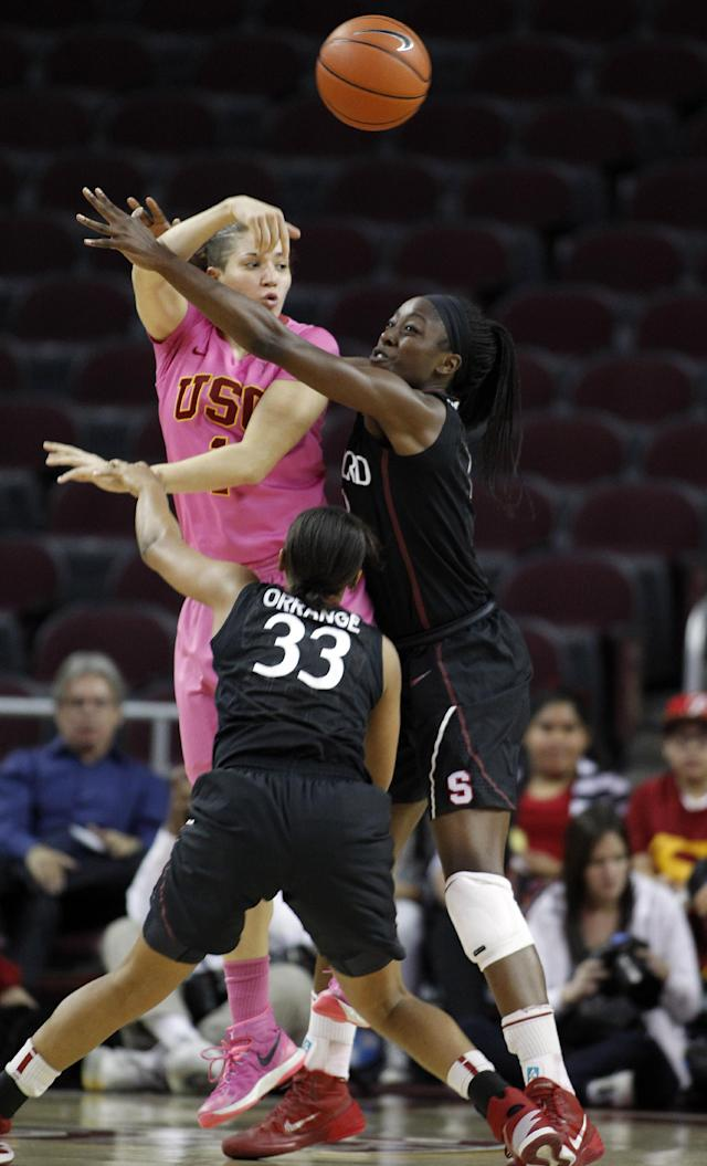 Southern California guard Jordan Adams, left, passes the ball away from Stanford guard Amber Orrange (33) and forward Chiney Ogwumike, right, during the first half of an NCAA college basketball game Friday, Feb. 21, 2014, in Los Angeles. (AP Photo/Alex Gallardo)