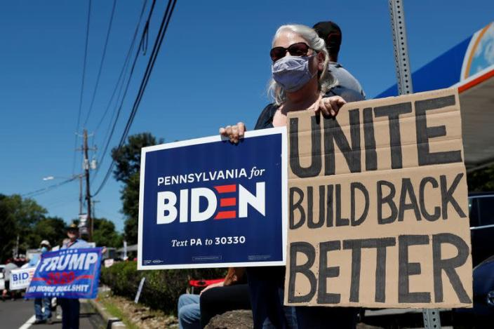 FILE PHOTO: A woman holds a sign in support of Democratic presidential nominee Joe Biden as supporters of U.S. President Donald Trump gather ahead of his campaign stop in Old Forge