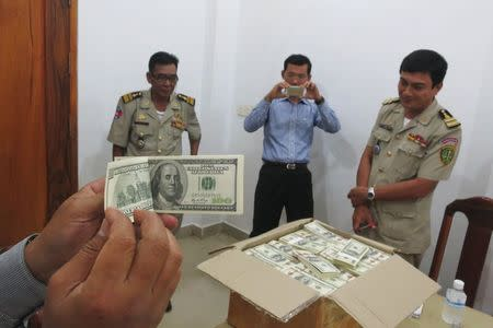 Police and court officials examine notes from a seized haul of $7.16 million in counterfeit hundred-dollar bills, in Battambang