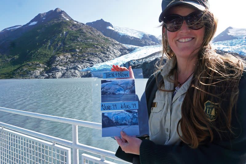 Chugach National Forest ranger Megan Parsley holds photos showing this summer's ice loss at the face of Portage Glacier