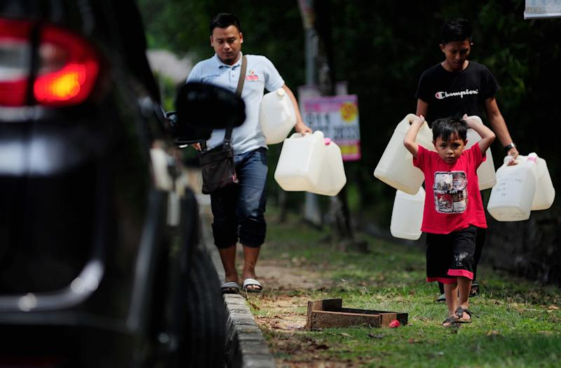 A boy carries plastic containers to a public water tap in Shah Alam April 24, 2019. — Bernama pic