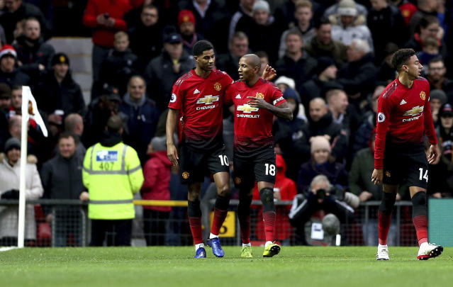 Manchester United's Ashley Young, center right, celebrates scoring his side's first goal of the game with teammate Marcus Rashford during their English Premier League soccer match against Fulham at Old Trafford, Manchester, England, Saturday, Dec. 8, 2018. (Barrington Coombs/PA via AP)