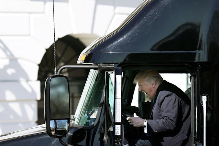 Trump reacts as he sits in a truck on March 23 while welcoming truckers and CEOs to attend a meeting at the White House regarding health care.