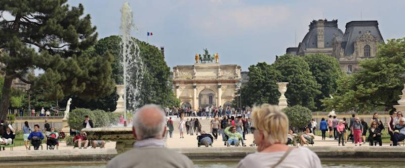 Paris, France - May 16, 2018: Senior couple sit in chairs at a fountain in the Tuileries gardens in Paris, France on May 16, 2018