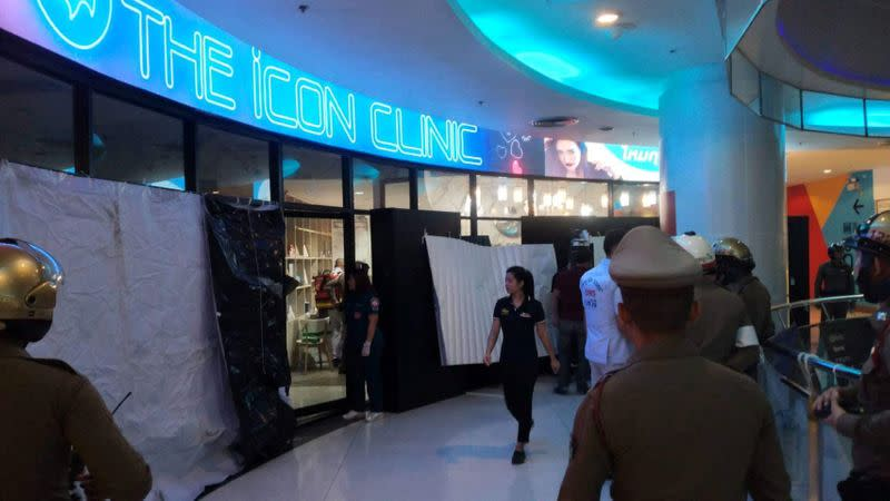 Emergency services are seen in front of a cosmetic clinic after a shooting at a shopping mall in Bangkok
