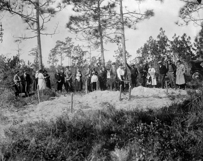 """White residents of Sumner stand near three graves of six Black victims who were killed in Rosewood. <span class=""""copyright"""">Bettmann Archive/Getty Images</span>"""