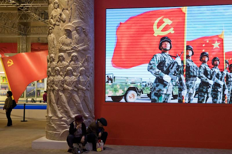 Thursday, Oct. 19, 2017, photo, an elderly couple rests under a screen showing Chinese soldiers posing with the Communist Party flag at an exhibition highlighting China's achievements under five years of his leadership at the Beijing Exhibition Hall in Beijing. Xi is channeling a red-blooded nationalism as he seeks to strengthen the Communist Party's role in Chinese life and assert Beijing's rise as a global superpower. Xi's muscular foreign policy could become even more assertive following this month's party congress, where he's expected to get a second five-year term as party secretary general. (AP Photo/Ng Han Guan)