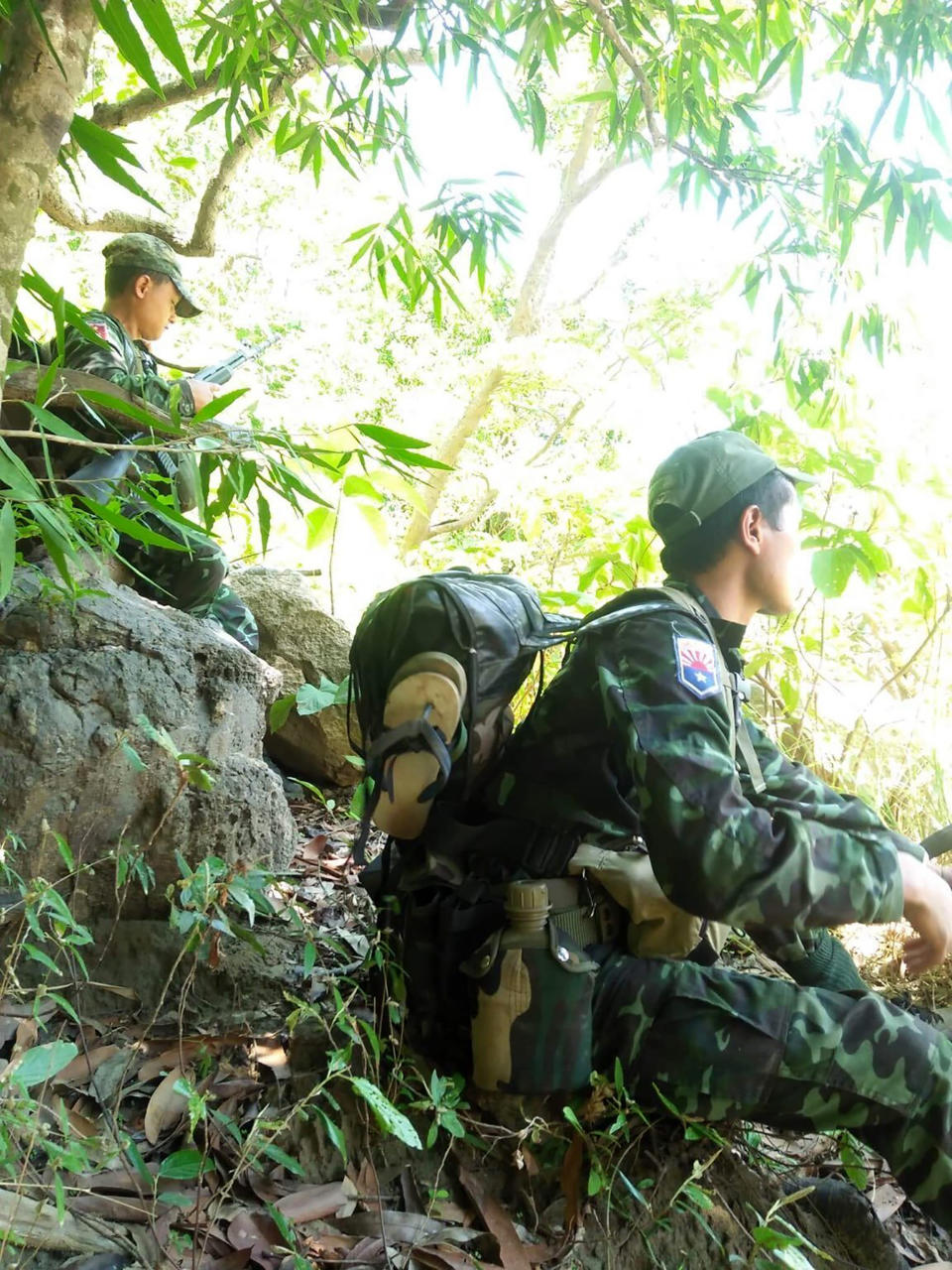 In this photo provided by Karen National Liberation Army, soldiers of the Karen National Liberation Army are seated in a forest Friday, May 7, 2021, in Mutraw district, Karen State, Myanmar. Ethnic Karen guerrillas burned down a Myanmar military outpost Friday morning, capturing it without a fight after its garrison fled at their approach, a senior Karen officer said. (Karen National Liberation Army via AP)