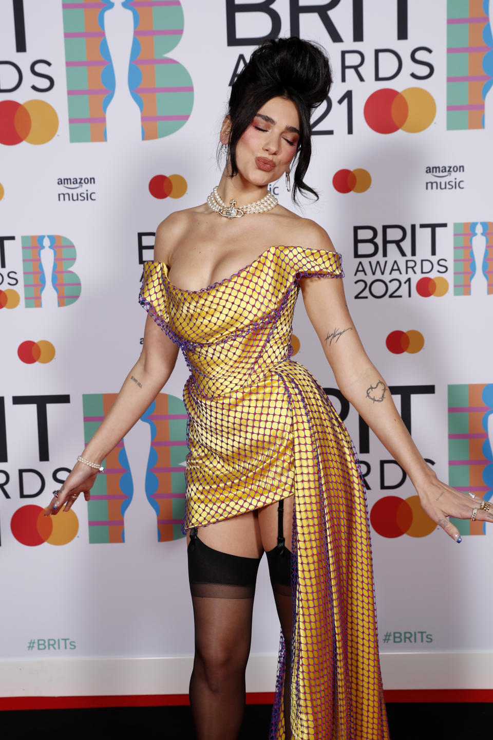 Dua Lipa poses in a yellow Vivienne Westwood mini dress with a train in the media room during The BRIT Awards 2021 at The O2 Arena on May 11, 2021 in London, England