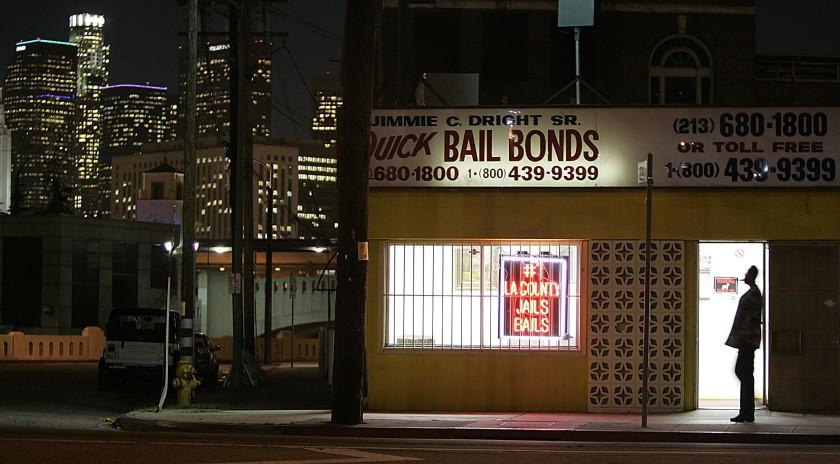 Gauthier, Robert –– – 093232.ME.0207.bail1.RCG –– The lights of downtown Los Angeles shine behind the Quick Bail Bonds building on Vignes Street across from Men's Central Jail, Monday, February 7, 2005.