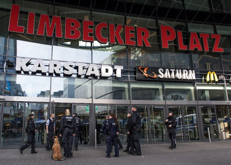 "Policemen with a sniffer dog stand in front of the ""Limbecker Platz"" shopping centre in Essen, western Germany, on March 11, 2017"