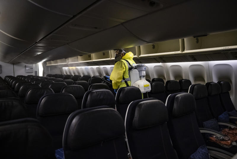 A member of Charles de Gaulle airport personnel sprays a liquid in the interior of an Air France aircraft as part of a disinfection process for airplanes in Terminal 2 of Charles de Gaulle international airport in Roissy, north of Paris, Thursday, May 14 2020. France began a gradual easing of its lockdown measures and restrictions amid the COVID-19 pandemic. (Ian Langsdon, Pool via AP)