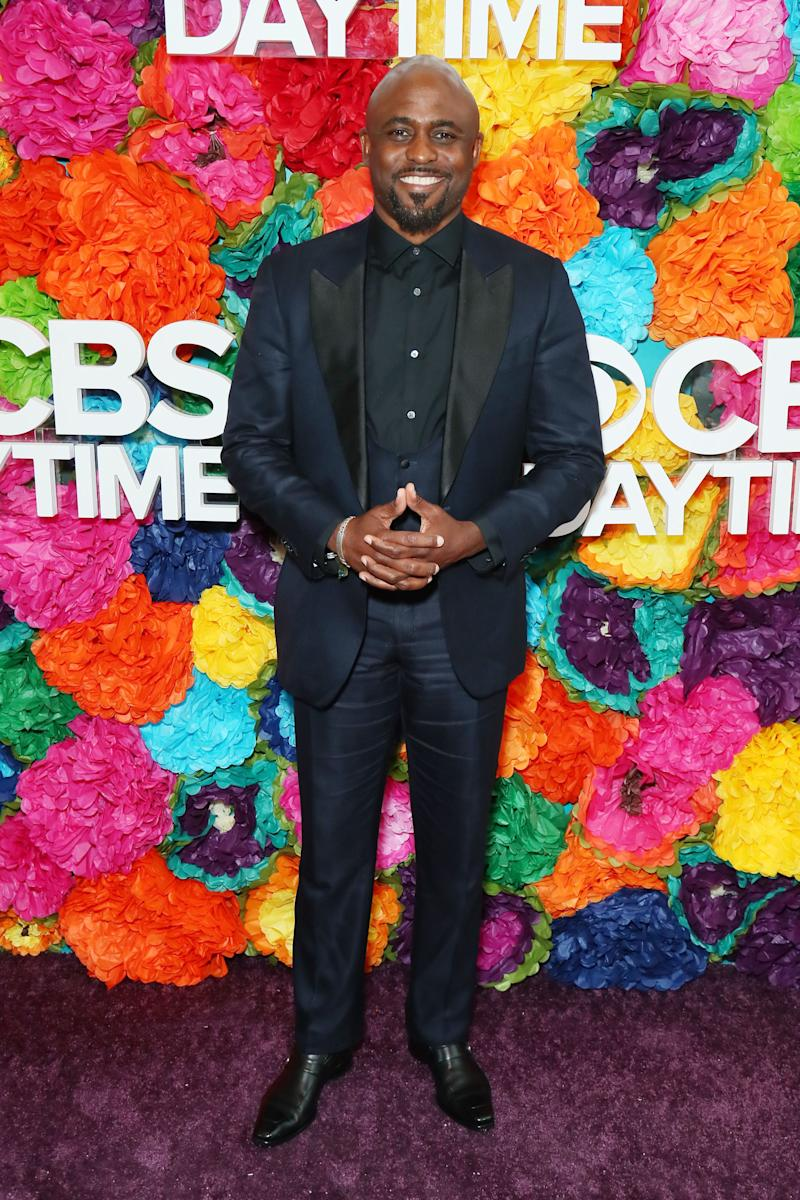 Wayne Brady wears a suit jacket and stands in front of a floral wall