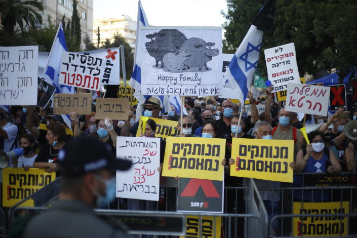 """Protesters, defying orders to maintain social distancing requirements, chant slogans and blew horns outside of the Prime Minister's residence in Jerusalem, Tuesday, July 14, 2020. Thousands of Israelis demonstrated outside of the official residence of Benjamin Netanyahu, calling on the embattled Israeli leader to resign as he faces a trial on corruption charges and grapples with a deepening coronavirus crisis. The signs read: """"you are detached. We are fed up."""" (AP Photo/Ariel Schalit)"""