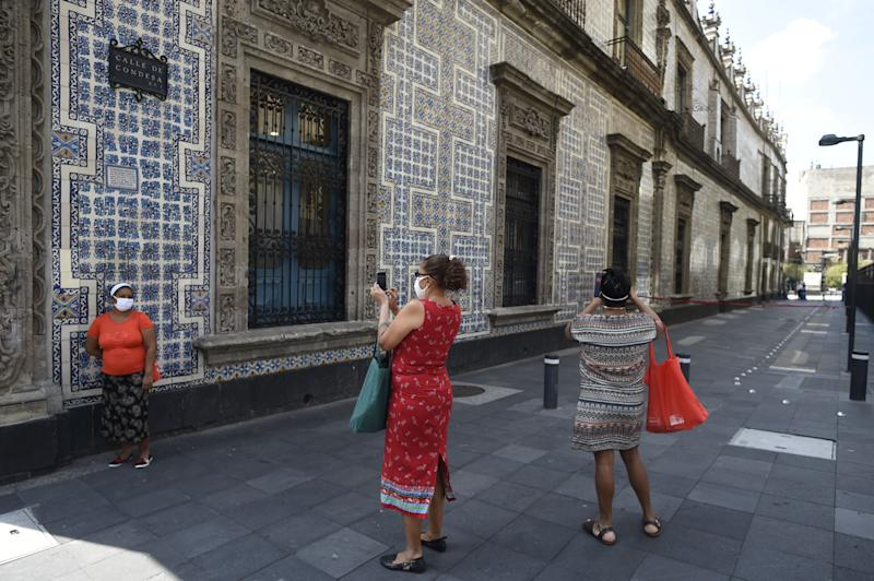 Women take pictures in Mexico City on July 1, 2020 during the COVID-19 pandemic. - Starting this week Mexico City is allowing the reopening of restaurants, shops, street markets and athletic complexes but with limited capacity and hours. (Photo by ALFREDO ESTRELLA / AFP) (Photo by ALFREDO ESTRELLA/AFP via Getty Images)