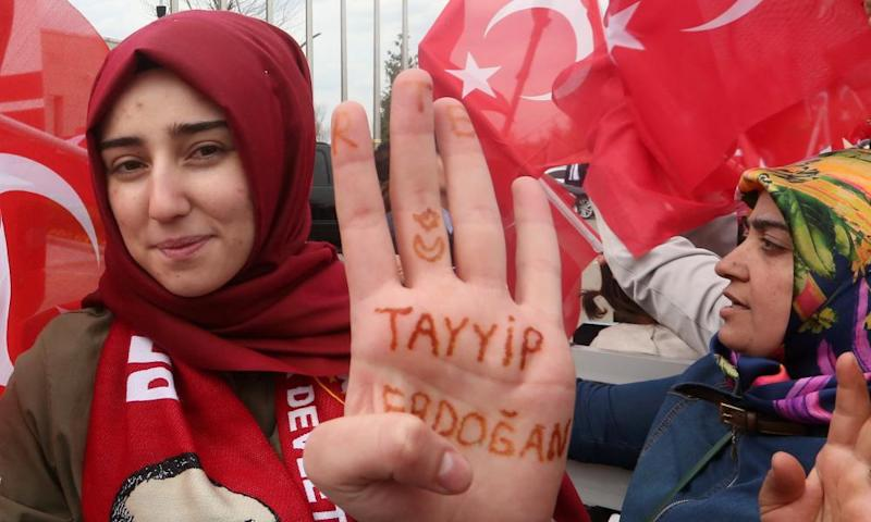 A woman shows her hand, which reads 'Tayyip Erdoğan', as she waits for the arrival of the Turkish president at Esenboğa airport in Ankara.