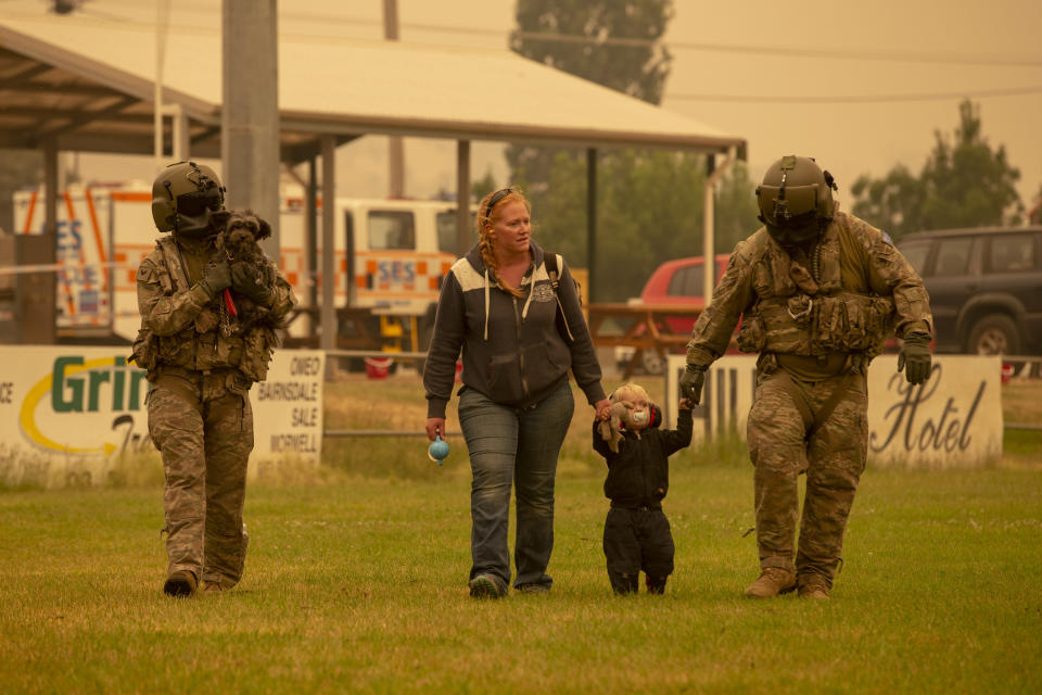 Two Australian Army Soldiers help people evacuate at Omeo showgrounds.
