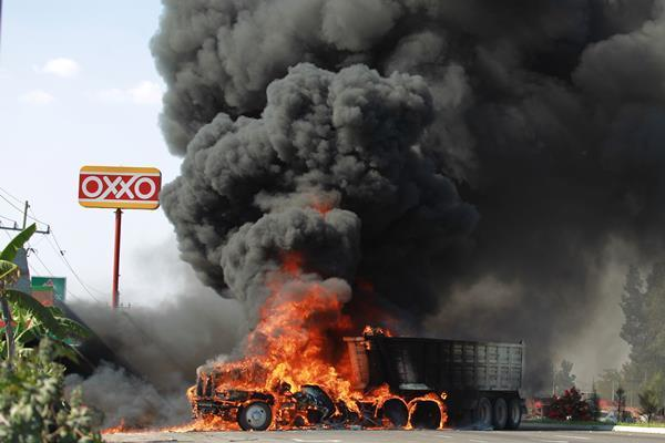 A truck burns on the road in Guadalajara, Mexico, Friday, March 9, 2012. Drug criminals set 25 city buses and other vehicles on fire in 16 different places, spreading fear Friday afternoon throughout Mexico's second-largest city after an army operation, a