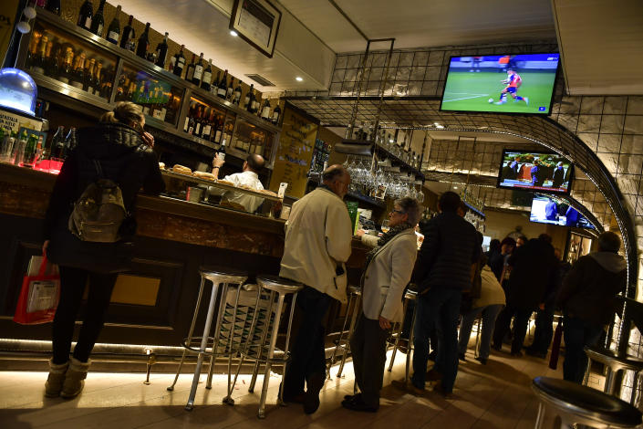 People watch Spanish TV channel in a bar with the breaking news of late Spanish dictator Francisco Franco's exhumation, on centre screen, in the basque city of Vitoria, northern Spain, Thursday, Oct. 24 2019. Forty-four years after his demise, the remains of Spanish dictator Gen. Francisco are to be dug out of his grandiose resting place outside Madrid and taken to a small family crypt, finally satisfying a long-standing demand of his victims' relatives and others who suffered under his regime. (AP Photo/Alvaro Barrientos)