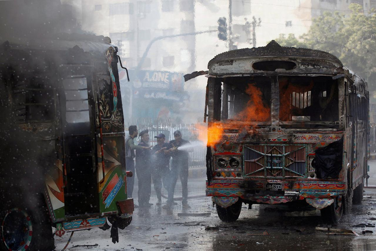 Firefighters douse a fire on buses, which according to local media were set ablaze by people after a girl was killed due to over speeding, along a road in Karachi, Pakistan November 24, 2017. REUTERS/Akhtar Soomro     TPX IMAGES OF THE DAY