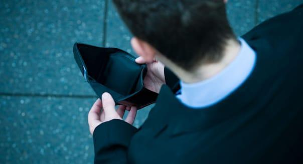 Young businessman checking his wallet