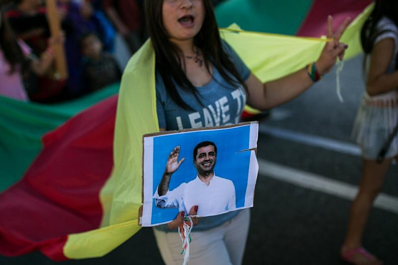 A Kurdish woman holds a photo of arrested HDP co-leader Selahattin Demirtas at a protest in Athens, Greece