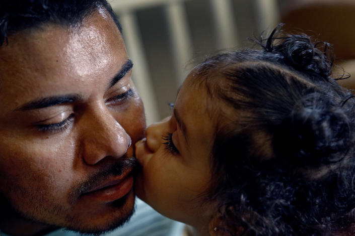 In this photo taken Tuesday, Aug. 28, 2018, Louis Alberto Enamorado Gomez gets a kiss from his daughter, Jeydi, 1, at their home in Grandview, Mo. Living in the U.S. since 2005, Gomez is fighting a deportation order stemming from a 2012 DUI charge because he fears what his removal would mean for his seven children, all U.S. citizens for whom he is the sole provider. (AP Photo/Charlie Riedel)
