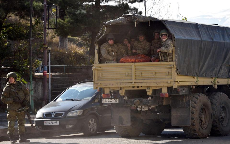 Azerbaijani soldiers ride in the back of a truck through the town of Lachin - KAREN MINASYAN/AFP via Getty Images