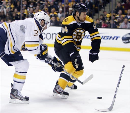 Boston Bruins' Joe Corvo (14) loses his stick while defending against Buffalo Sabres' Jordan Leopold (3) in the first period of an NHL hockey game in Boston, April 7, 2012. (AP Photo/Michael Dwyer)
