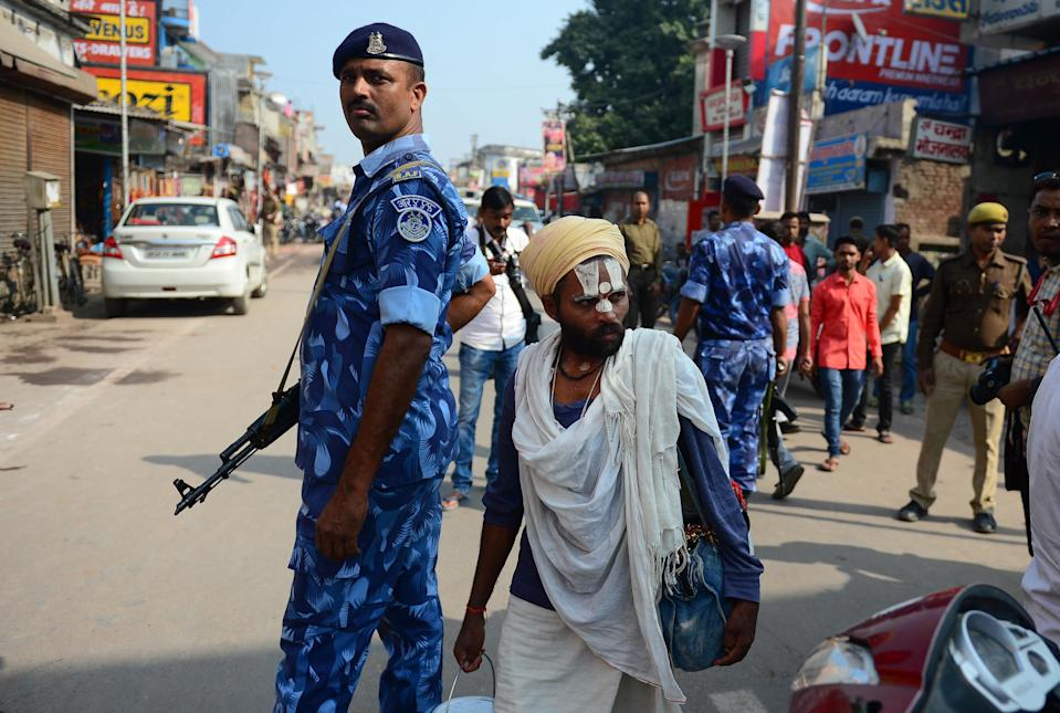 A Hindu man walks past security personnel on a road in Ayodhya on November 9, 2019, ahead of a Supreme Court verdict on the disputed religious site. - India braced on November 9 for a Supreme Court ruling over a holy site contested for centuries by Hindus and Muslims, which in 1992 sparked some of the deadliest sectarian violence since independence. (Photo by SANJAY KANOJIA / AFP) (Photo by SANJAY KANOJIA/AFP via Getty Images)