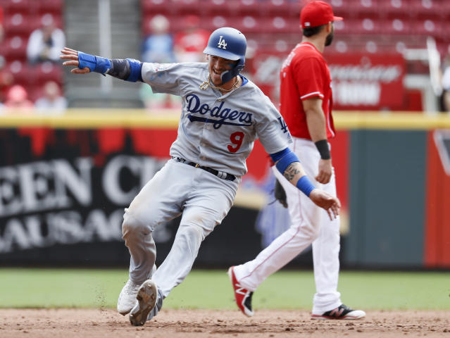 FILE - In this Sept. 12, 2018, file photo, Los Angeles Dodgers' Yasmani Grandal advances to second on an error by Cincinnati Reds second baseman Scooter Gennett during a baseball game in Cincinnati. A person familiar with the negotiations tells The Associated Press that Grandal and the Milwaukee Brewers have agreed to a one-year contract. The person spoke on condition of anonymity Wednesday, Jan. 9, because the agreement, first reported by The Athletic, was subject to a successful physical. (AP Photo/John Minchillo, File)