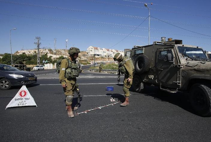 Israeli soldiers set up a checkpoint on the road near the Jewish West Bank settlement of Kiryat Arba, on June 30, 2016 (AFP Photo/Hazem Bader)