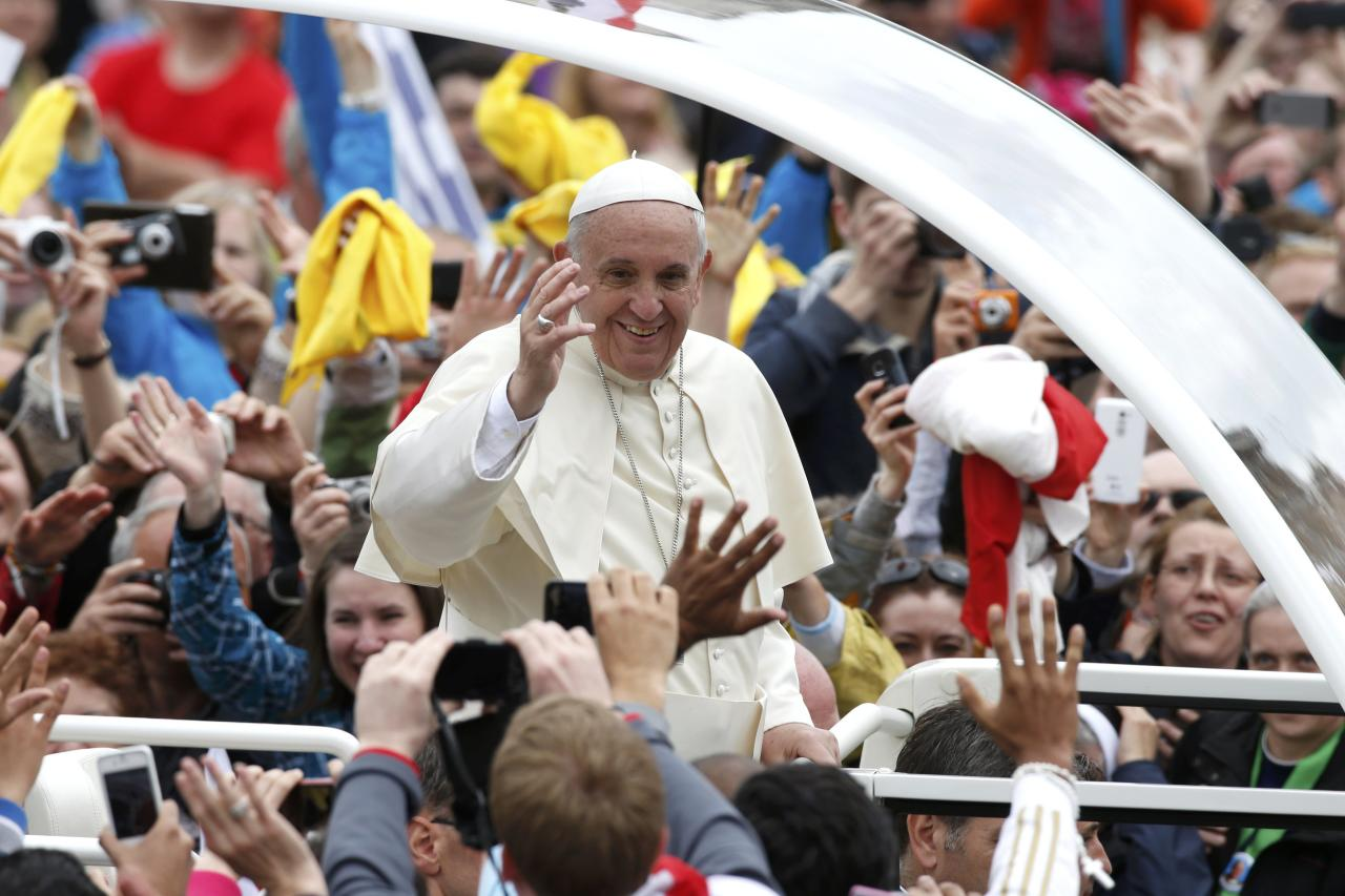 Pope Francis greets the faithful as he rides in his Popemobile after the canonisation ceremony of Popes John XXIII and John Paul II in St. Peter's Square at the Vatican April 27, 2014. Pope John XXIII, who reigned from 1958 to 1963 and called the modernising Second Vatican Council, and Pope John Paul II, who reigned for nearly 27 years before his death in 2005 and whose trips around the world made him the most visible pope in history, were declared saints by Pope Francis at an unprecedented twin canonisation on Sunday. REUTERS/Tony Gentile (VATICAN - Tags: RELIGION)