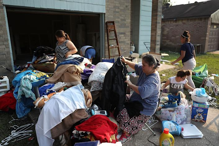 Axa Alvarez (holding coat) and her family sort through clothes on on Sept. 2 as they clean out their house, which had been inundated with water.