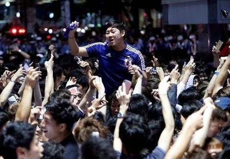 Soccer fans and pedestrians exchange high fives in praise of Japan's soccer team players near a diagonal crosswalk after World Cup Group H soccer match Japan vs Senegal, at Shibuya district in Tokyo, Japan June 25, 2018. REUTERS/Issei Kato