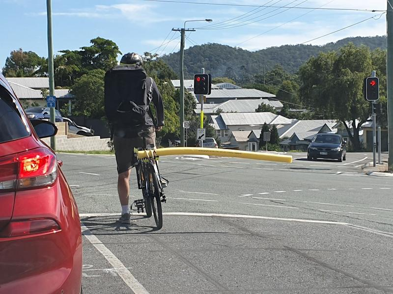 A Brisbane cyclist is stopped at traffic lights with a long yellow pool noodle extending from the right side of his bike. Source: Facebook