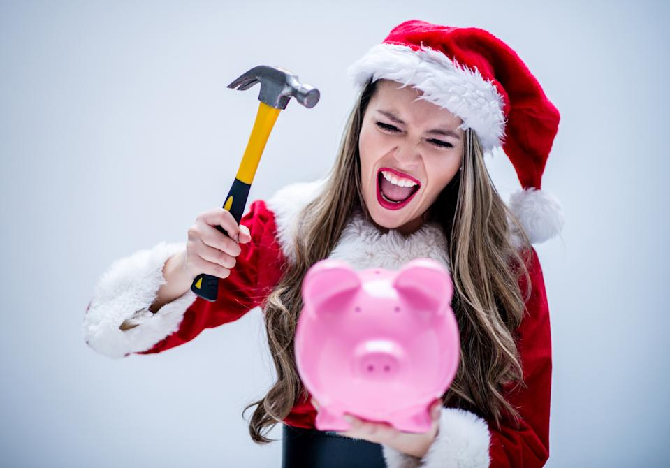 Angry female Santa breaking her piggybank with a hammer
