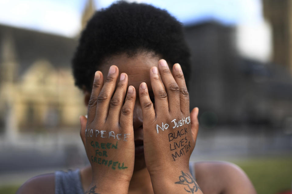 """FILE - In this file photo dated Sunday, June 21, 2020, a woman symbolically covers her eyes as she participates in a Black Lives Matter protest calling for an end to racial injustice, at the Parliament Square in central London. A government inquiry, by a panel of experts, has concluded Wednesday March 31, 2021, that there is racism in Britain, but it's not a systematically racist country that is """"rigged"""" against non-white people, though many ethnic-minority Britons greeted that claim with skepticism. (AP Photo/Alberto Pezzali)"""