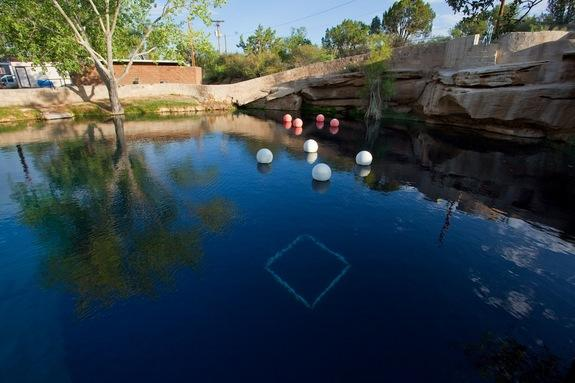 """The surface of the """"Blue Hole"""" in Santa Rosa, N.M. The balloons hold up underwater scuba stations used to train divers."""