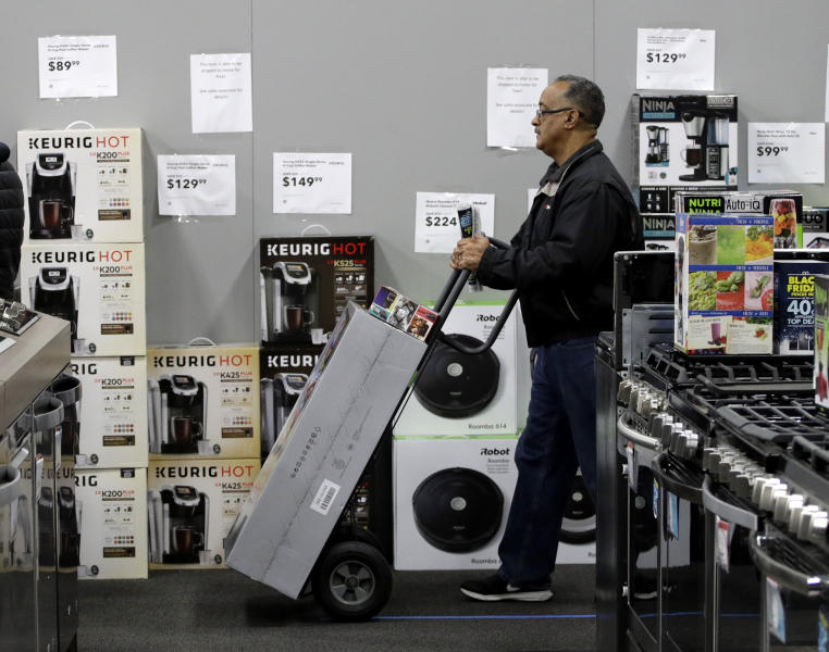 A man waits to check out as he shops a Black Friday sale at a Best Buy store on Thanksgiving Day, Thursday, Nov. 23, 2017, in Overland Park, Kan. Shoppers are hitting the stores on Thanksgiving as retailers under pressure look for ways to poach shoppers from their rivals. (AP Photo/Charlie Riedel)