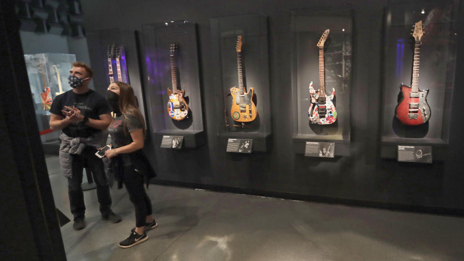Two people look at an exhibit at the Rock and Roll Hall of Fame, Monday, June 15, 2020, in Cleveland. The Rock & Roll Hall of Fame reopened to the public on Monday with new health and safety precautions in place to protect staff and guests. (AP Photo/Tony Dejak)