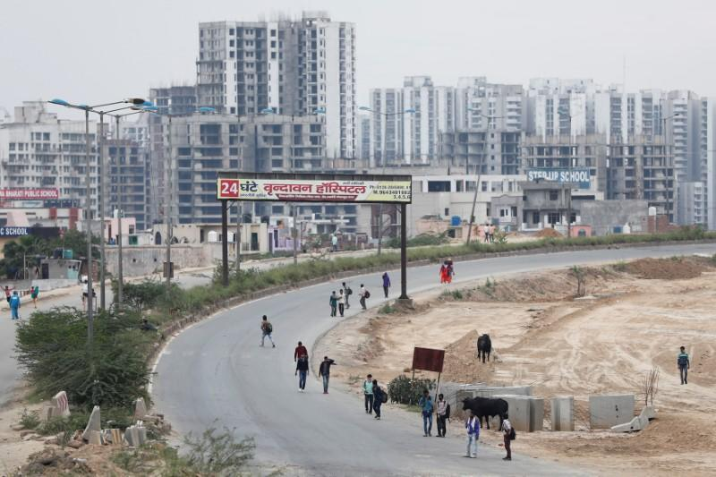 Migrant workers walk on a highway with their families as they look out for a transport to return to their villages, after India ordered a 21-day nationwide lockdown to limit the spreading of coronavirus disease (COVID-19), in Ghaziabad
