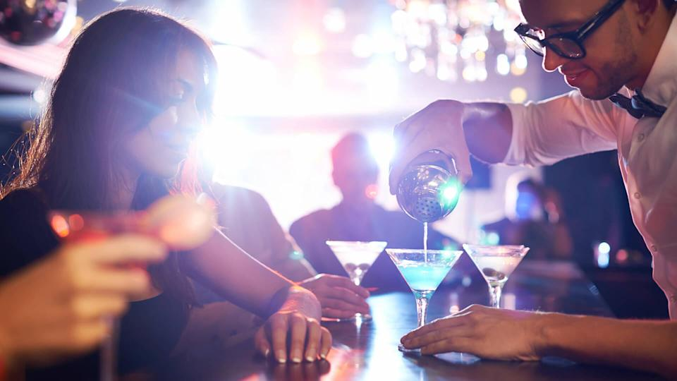 Barman pouring alcohol pouring cocktail for attractive girl.